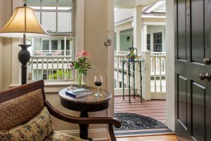 Room 14 at The Addison on Amelia Island - End table with chair and view to the porch
