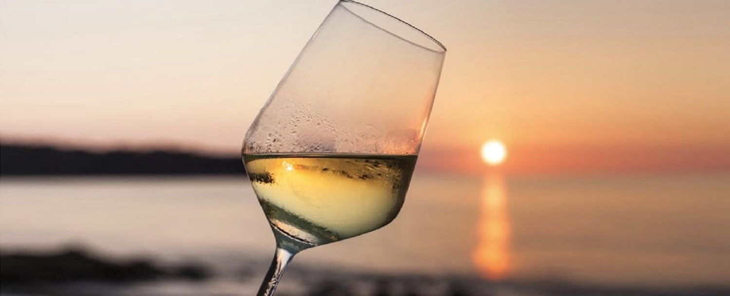 Wine glass with sunset on the beach behind it on Amelia Island