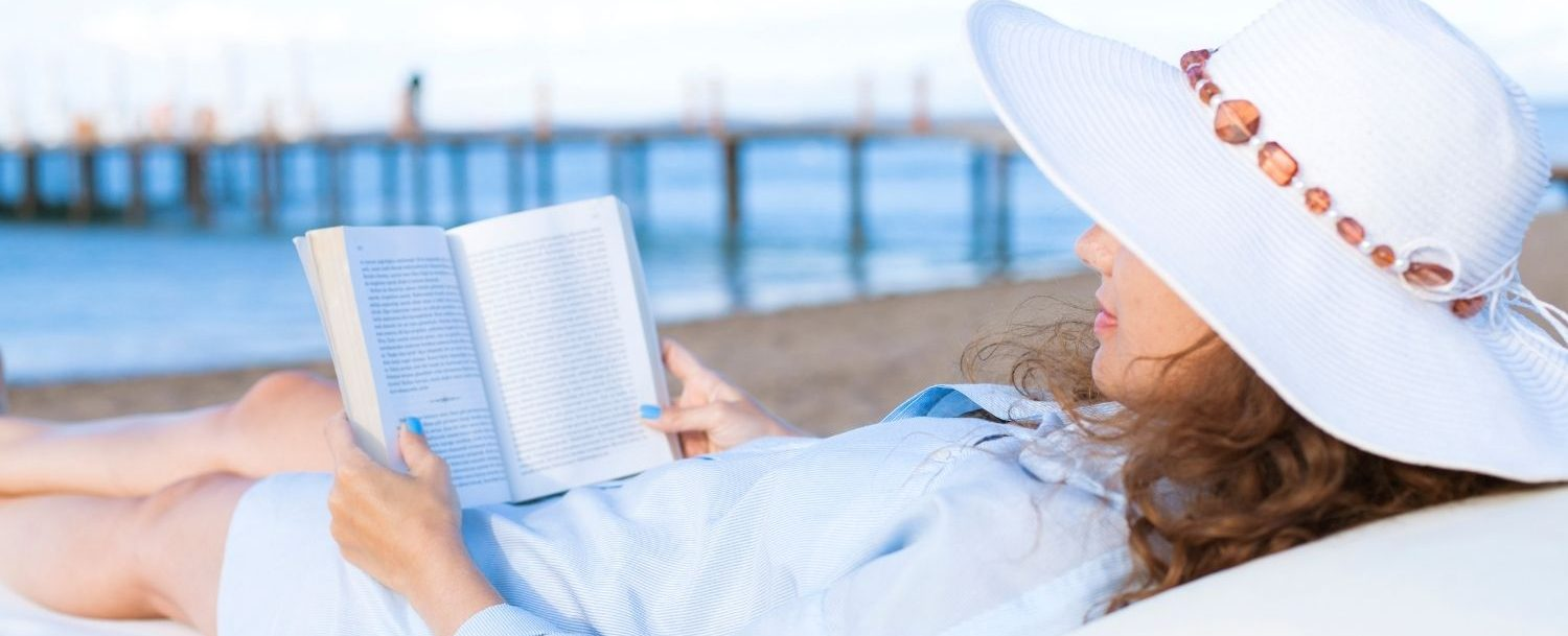 Lady reading a book on the beach.