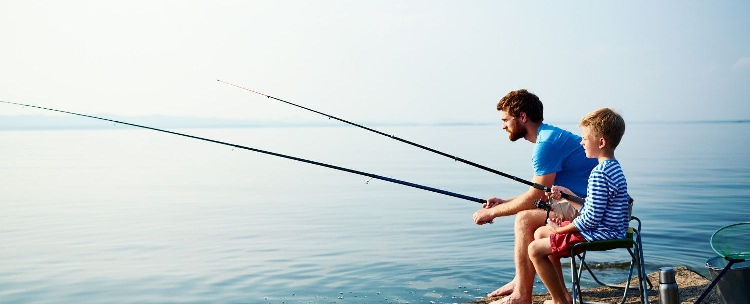 Dad and son fishing off shore.