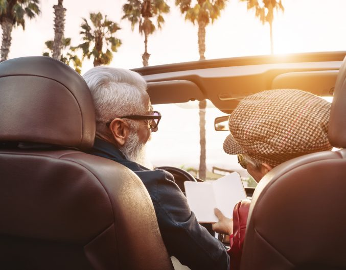 Happy senior couple having fun on new convertible car - Mature people enjoying time together during road trip vacation - Elderly lifestyle and travel transportation concept (Happy senior couple having fun on new convertible car - Mature people enjoyin