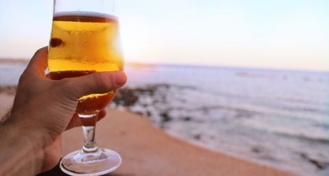 Person holding a beer by the ocean