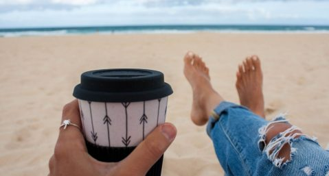 Woman sitting on the beach holding coffee.