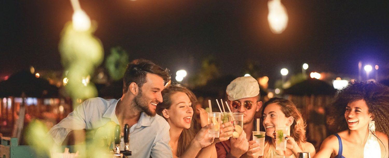 Group of friends at a bar at night.